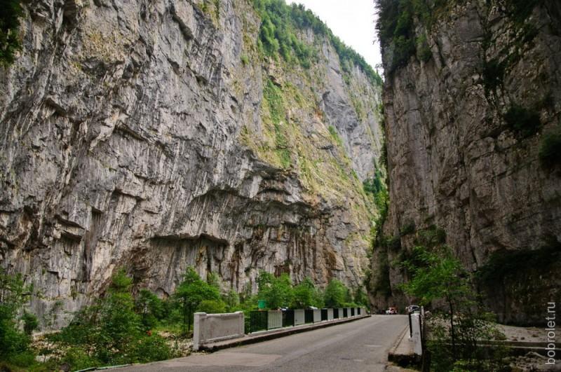 Огромные скалы нависают с двух сторон над дорогой, создавая ощущение, что стоишь в гигантской каменной вазе.