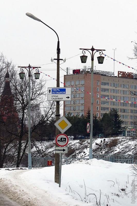 А это обременённый дорожными знаками большой фонарь в компании фонарей пониже ростом и посимпатичнее.