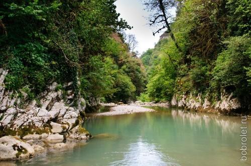 Путь к каньону лежит вдоль реки с каменистыми берегами.